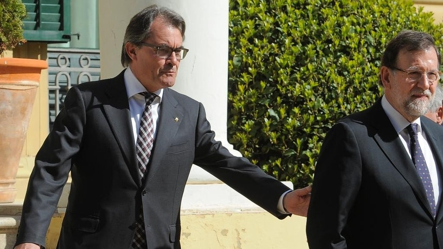 Spanish Prime Minister, Mariano Rajoy, right, and Catalan regional government Artur Mas, gesture before the informal Ministerial meeting gathering foreign ministers from the European Union and the southern Mediterranean nations in Barcelona, Spain, Monday, April 13, 2015. Foreign ministers from European and North African countries have gathered in Barcelona to discuss ways to fight terrorism and illegal immigration. Europe has been hit by increasing waves of migration from Syrians and sub-Saharan Africans crossing the Mediterranean in flimsy boats in a bid to get to Europe. (AP Photo/Manu Fernandez)