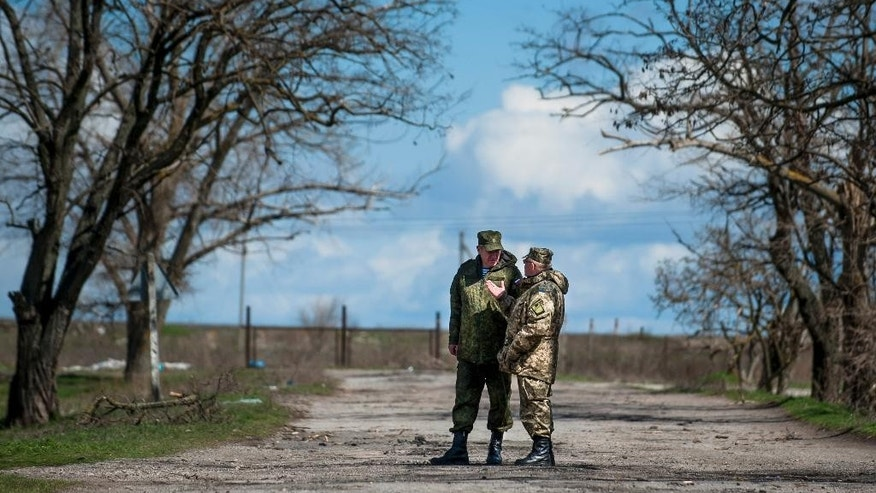 Russian General Alexander Lentsov speaks with Ukrainian General Alexander Rozmaznin in Shyrokyne village, eastern Ukraine, Thursday, April 9, 2015. The OSCE also reported intense mortar fire outside the village of Shyrokyne by the Azov Sea but said its representatives were repeatedly barred from accessing the village on Sunday, April 12, 2015. (AP Photo/Evgeniy Maloletka)