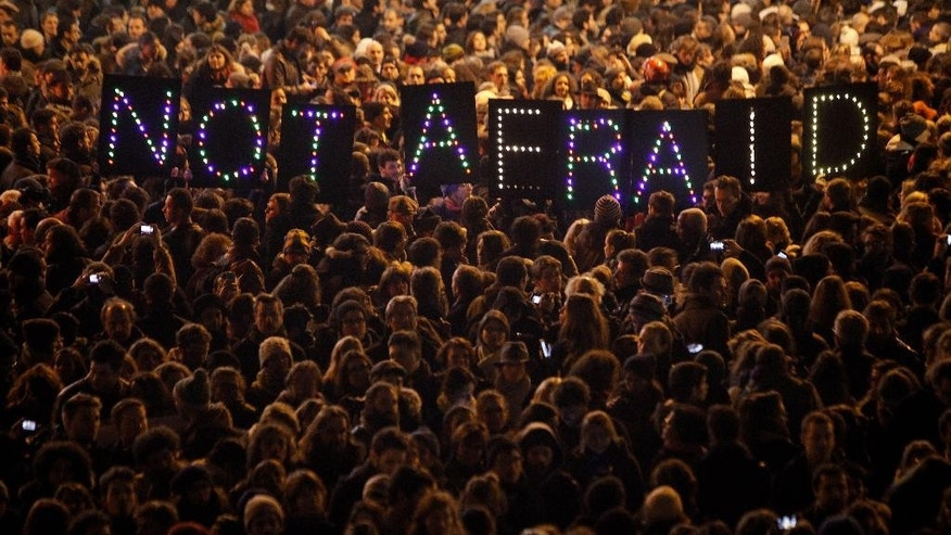 "FILE- This Wednesday, Jan. 7, 2015 file photo shows people gathering in solidarity of the victims of a terror attack against a satirical newspaper, in Paris, France. France's prime minister Manuel Valls called for the introduction in an intelligence bill of an emergency procedure allowing the government to use surveillance powers with no delay in case of exceptional threat. The measure would be used only ""in case of major crisis affecting the citizens' security"", Valls said Monday in a speech at France's lower house of Parliament. (AP Photo/Thibault Camus, File)"