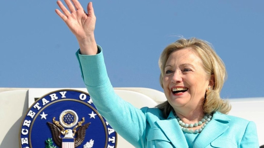 FILE - In this June 10, 2011, file photo, then-Secretary of State Hillary Rodham Clinton waves as the arrives at Lusaka International Airport in Lusaka, Zambia. Clinton confidantes view her four years at the helm of the State Department as her golden era _ a chance for one of the country's most polarizing figures to jump off the political treadmill. She set a record for international travel and prioritized issues she had long been passionate about, including global health and boosting opportunities for women and girls. (AP Photo/Susan Walsh, Pool, File)