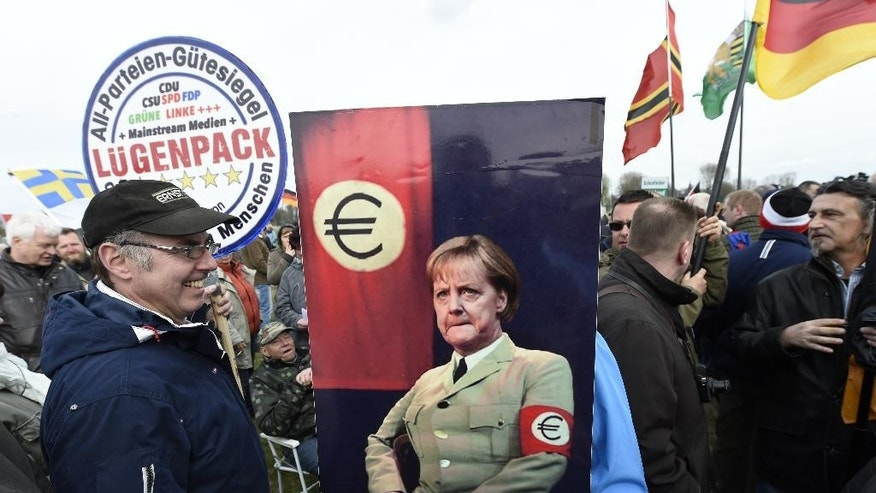 Participants hold a poster depicting German Chancellor Angela Merkel in a jacket that resembles Third Reich uniforms with a Euro sign on the sleeve at a rally called 'Patriotic Europeans against the Islamization of the West' (PEGIDA) demonstrate in Dresden, Germany, Monday, April 13, 2015. (AP Photo/Jens Meyer)