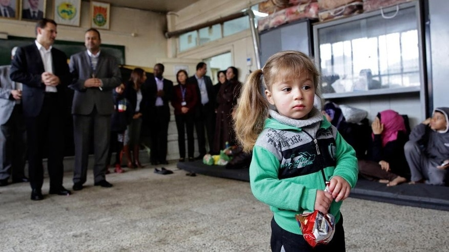 A girl holds a snack at a school, during the visit of Pierre Krahenbuhl, commissioner-general of the United Nations Relief and Works Agency (UNRWA), background left, in Yarmouk refugee camp in Damascus, Syria, Sunday, April 12, 2015. Krahenbuhl, visited refugees fro  visited refugees from the embattled Palestinian camp of Yarmouk in Damascus. The Palestinians fled Yarmouk, where heavy fighting has raged since Islamic State militants stormed the district more than a week ago, for a nearby government-controlled area of the Syrian capital. (AP Photo)