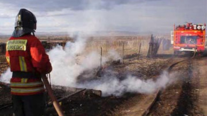 In this undated photo taken from the Website of the Ministry for Emergency Situations, Khakassia branch Monday, April 13, 2015, a firefighter extinguishes the fire in Khakassia, a region in southeastern Siberia, Russia. Russian authorities say out-of-control agricultural fires have killed at least 15 people, injured hundreds more and destroyed or damaged more than 1,000 homes in Siberia. The fires were started by farmers burning the grass in their fields, but spread quickly because of strong winds. (Ministry for Emergency Situations, Khakassia branch in Siberia via AP)
