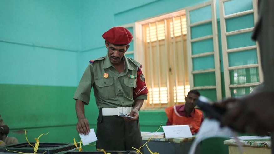 A member of the Sudanese security forces casts his ballot at a polling station on the first day of Sudan's presidential and legislative elections, in Khartoum, Sudan, Monday, April 13, 2015. (AP Photo/Mosa'ab Elshamy)