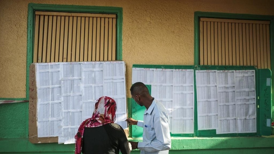 A couple look for their names on lists of eligible voters outside a polling station, on the first day of Sudan's presidential and legislative elections, in Khartoum, Sudan, Monday, April 13, 2015. (AP Photo/Mosa'ab Elshamy)