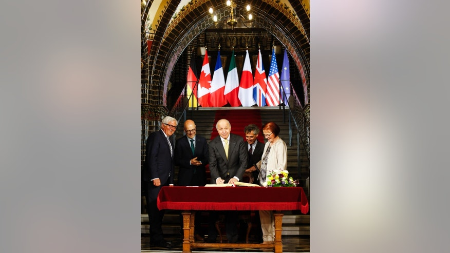 French Foreign Minister Laurent Fabius, center, signs the Golden Book of the city of Luebeck prior to a meeting of the G7 Foreign ministers in Luebeck, northern Germany, Tuesday, April 14, 2015. The meeting is being held ahead of the G7 leaders summit in Germany from June 7 to 8, 2015. The other people attending the ceremony are German Foreign Minister Frank-Walter Steinmeier, left, Prime Minister of the German State Schleswig-Holstein Torsten Albig, 2nd from left, the mayor of Luebeck Bernd Saxe and city representative Gabriele Schopenhauer, right. (AP Photo/Markus Schreiber, Pool)