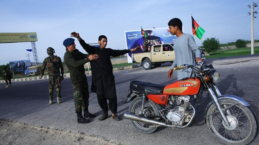 In this Sunday, April 12, 2015 photo, An Afghan National Army soldier searches a civilian on a road in Herat city, west of capital Kabul. Afghanistan could face a war with the Islamic State group if the government does not resolve internal differences and improve the security situation, one of the country's most powerful warlords warned in an interview with The Associated Press. (AP Photo/Massoud Hossaini)