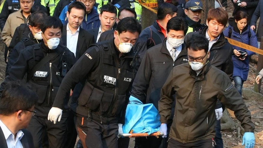 In this April 9, 2015 photo, South Korean police officers carry the body of Sung Wan-jong in Seoul, South Korea. South Korean President Park Geun-hye faced charges Wednesday, April 15, 2015 that members of her administration received bribes from the businessman found dead in an apparent suicide last week. (Kim Ju-sung/Yonhap via AP) KOREA OUT