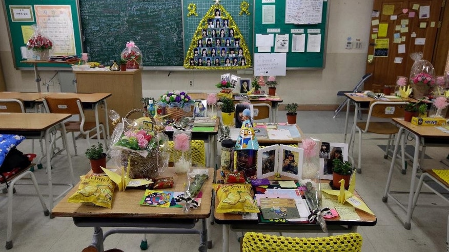 In this April 8, 2015, photo, flowers, letters and gifts are left on victims' desks at a classroom at Danwon High School in Ansan, south of Seoul, South Korea. One year ago the ferry Sewol carrying 325 second-year students on a field trip to a southern island sank; only 75 survived. Their classrooms in this city about an hour south of Seoul have barely changed from the day they left for the trip. (AP Photo/Lee Jin-man)