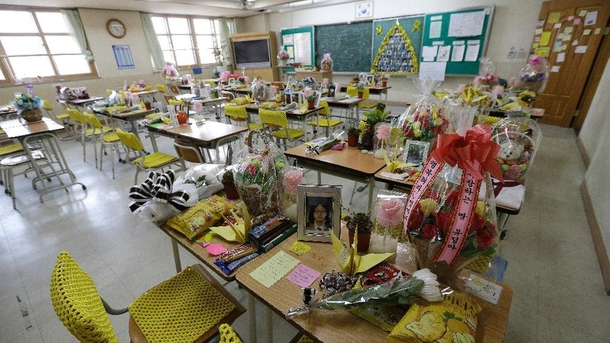 In this April 10, 2015, photo, flowers, notes and snacks from classmates and family paying tribute to the victims of the sinking of ferry Sewol are placed on the desks in a classroom at Danwon High School in Ansan, South Korea. Surrounded by the buzz of regular school life, a few classrooms at Danwon High School stand apart. They have become part shrine, part refuge, part confessional. The Sewol ferry sank on April 16, 2014, killing 304 people including 250 Danwon High School students on a school trip. (AP Photo/Ahn Young-joon)