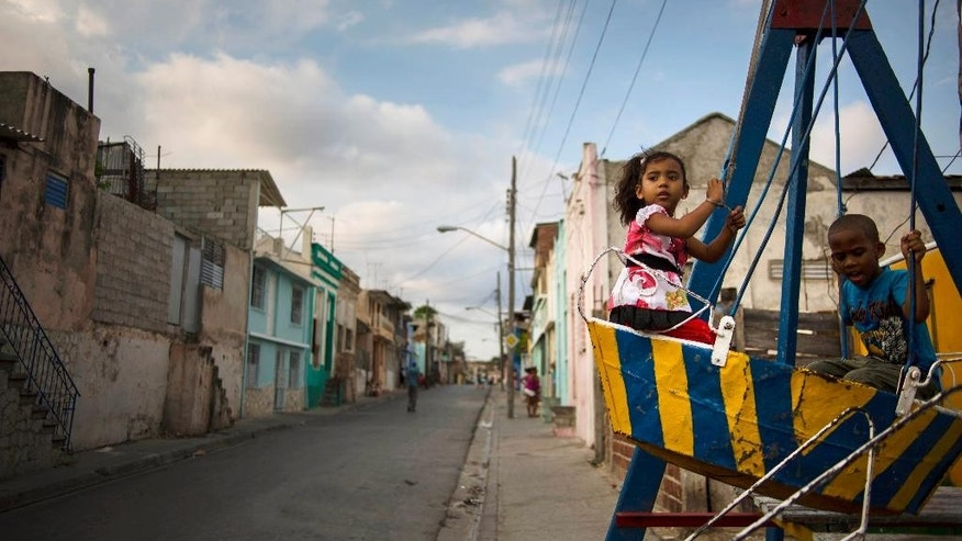 In this March 21, 2015 photo, children play on a swing in Santiago, Cuba. The playground was set up for a youth fair in their neighborhood, and will later be moved to other areas of the city. (AP Photo/Ramon Espinosa)