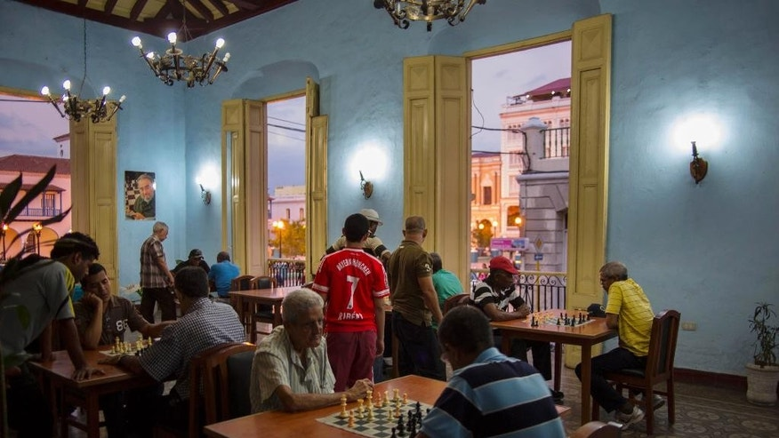 "In this March 21, 2015 photo, people play chess at a club in Santiago, Cuba. The ""Ajedrez Jose Raul Capablanca"" chess house is a club exclusively for chess playing, open to both men and women, and is adjunct to the Cathedral. (AP Photo/Ramon Espinosa)"