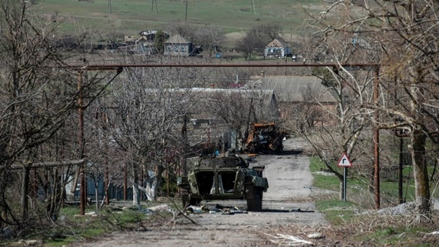 Friday April 10, 2015: A damaged armed vehicle of pro-Russian rebels stands between the positions of pro-Russian rebels and the Ukrainian army in Shyrokyne village, eastern Ukraine. (AP Photo/Evgeniy Maloletka)