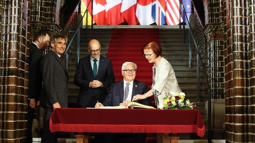 German Foreign Minister Frank-Walter Steinmeier, second right, signs the Golden Book of the city of Luebeck prior to a meeting of the G7 foreign ministers in Luebeck, northern Germany, Tuesday, April 14, 2015.  The meeting is being held ahead of the G7 leaders summit in Germany from June 7 to 8, 2015. (AP Photo/Markus Schreiber, Pool)