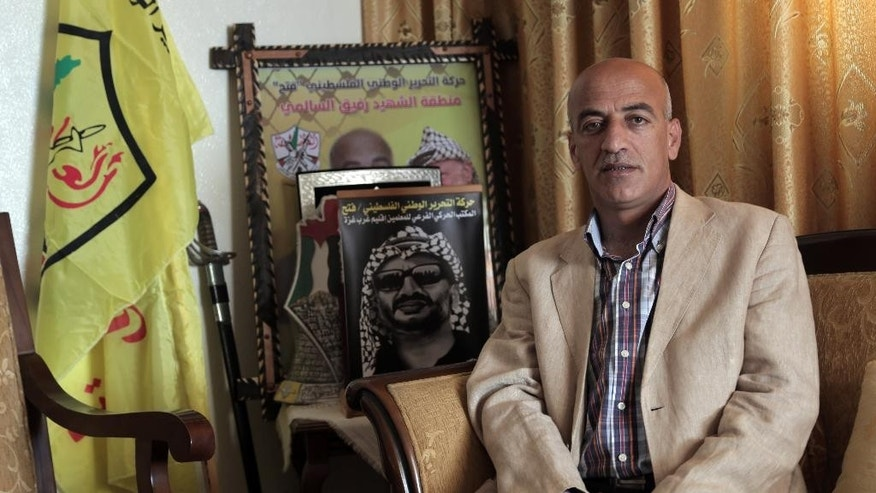 In this Thursday, April. 9, 2015 photo, Palestinian Ziyad Mattar poses  for a photograph next to Fatah movement flag and a poster of the late Fatah leader Yasser Arafat at his house in Gaza City. Mattar said he was held for six hours at an Hamas interrogation center on New Year's Day, as part of what he said were efforts to prevent the traditional rally on Fatah's founding anniversary.(AP Photo/Khalil Hamra)