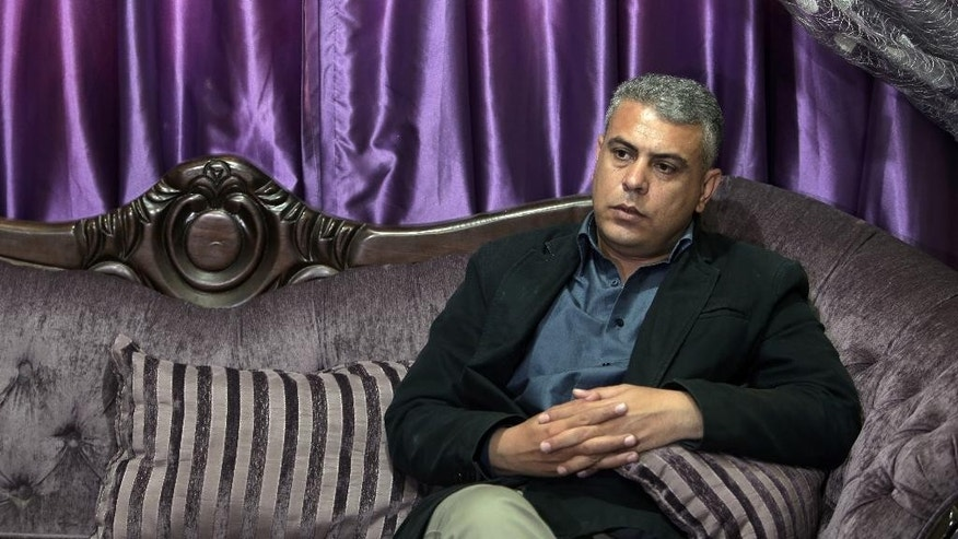 In this Sunday April, 5, 2015 photo, Palestinian Fatah activist Maamoun Sweidan speaks to the Associated Press during an interview in his house in Gaza City. Over the past two months, Hamas has banned him from travel, masked men have fired shots at his car, wounding two companions, and he was detained for five days without charges, Sweidan said. (AP Photo/Khalil Hamra)