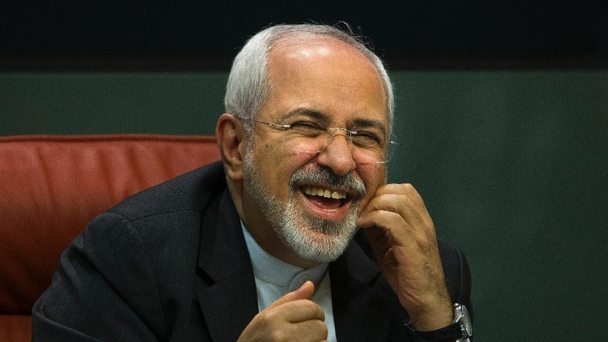 Iranian Foreign Minister Mohammad Javad Zarif  laughs during a press conference with his Spanish counterpart Manuel Garcia Margallo in Madrid,  Spain, Tuesday, April 14, 2015. (AP Photo/Andres Kudacki)