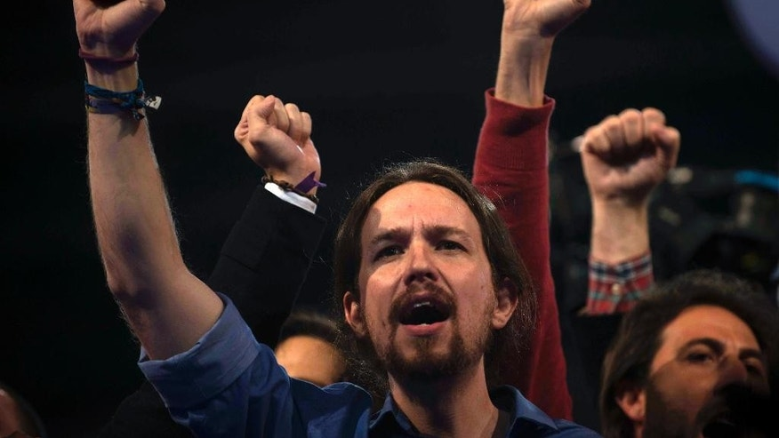 "FILE - In this March 20, 2015, file photo, Pablo Iglesias, the leader of Spain's new and growing far left 'Podemos' (""We Can"") party, raises his arm and sings the Andalusian anthem during an electoral campaign rally in Dos Hermanas, Sevilla, Spain. Two upstart parties that have emerged over the past year are mounting an unprecedented challenge to the governing Popular Party and the Socialist Party, which for four decades have dominated Spanish politics. A survey of voter intentions published Sunday in El Pais placed Podemos (""We Can"") and Ciudadanos (""Citizens"") roughly neck-and-neck with their long-established rivals ahead of next month's local and regional elections. The four were separated by less than three percentage points. (AP Photo/Laura Leon, File)"