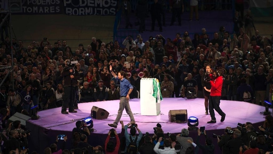 "FILE - This March 20, 2015, file photo shows the Pablo Iglesias, the leader of Spain's new and growing far left 'Podemos' (""We Can"") party, waving to the crowd during an electoral campaign rally in Dos Hermanas, Seville, Spain. Two upstart parties that have emerged over the past year are mounting an unprecedented challenge to the governing Popular Party and the Socialist Party, which for four decades have dominated Spanish politics. A survey of voter intentions published Sunday in El Pais placed Podemos (""We Can"") and Ciudadanos (""Citizens"") roughly neck-and-neck with their long-established rivals ahead of next month's local and regional elections. The four were separated by less than three percentage points. (AP Photo/Laura Leon, File)"