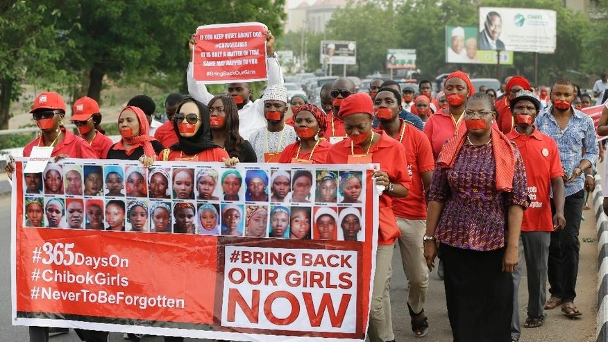 People march during a silent protest calling on the government to rescue the kidnapped girls of the government secondary school in Chibok, who were abducted a year ago, in Abuja, Nigeria, Monday, April 13, 2015. Nearly 300 schoolgirls from Chibok were abducted in a mass kidnapping on the night of April 14-15. Dozens escaped on their own but 219 remain missing.  (AP Photo/Sunday Alamba)
