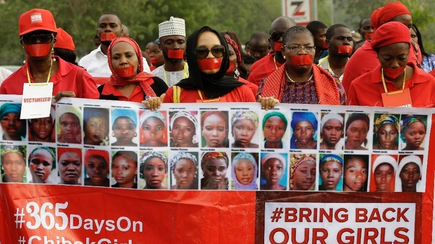 People march on a street during a silent protest calling on the government to rescue the kidnapped girls of the government secondary school in Chibok, who were kidnapped a year ago, in Abuja, Nigeria, Monday, April 13, 2015. Nearly 300 schoolgirls from Chibok were abducted in a mass kidnapping on the night of April 14-15. Dozens escaped on their own but 219 remain missing. (AP Photo/Sunday Alamba)