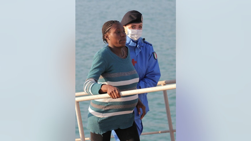 A pregnant woman is helped disembark as migrants arrive at the Sicilian Porto Empedocle harbor, Italy, Monday, April 13, 2015. Italy's Coast Guard helped save 144 migrants Monday from a capsized boat in the waters off Libya and spotted nine bodies. It was the most dramatic of numerous rescue operations that brought thousands to safety in recent days, as good weather has encouraged the desperate to set out on smugglers' vessels. The overturned boat was spotted 80 miles north of Libya, Coast Guard Cmdr. Filippo Marini told The Associated Press in a telephone interview. (AP Photo/Calogero Montanalampo)