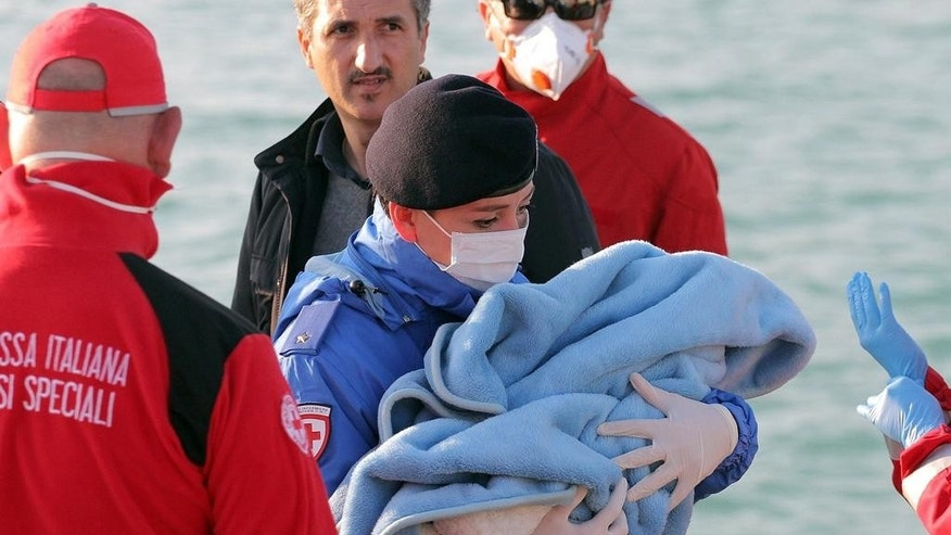 A Red Cross volunteer carries a baby wrapped in a blanket after migrants disembarked at the Sicilian Porto Empedocle harbor, Italy, Monday, April 13, 2015. Italy's Coast Guard helped save 144 migrants Monday from a capsized boat in the waters off Libya and spotted nine bodies. It was the most dramatic of numerous rescue operations that brought thousands to safety in recent days, as good weather has encouraged the desperate to set out on smugglers' vessels. The overturned boat was spotted 80 miles north of Libya, Coast Guard Cmdr. Filippo Marini told The Associated Press in a telephone interview. (AP Photo/Calogero Montanalampo)