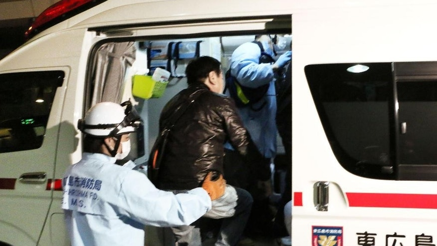 An injured passenger of an Asiana Airlines plane that skidded off a runway after landing at Hiroshima Airport is helped to get on an ambulance in Mihara, Hiroshima Prefecture, western Japan, Tuesday, April 14, 2015. The Hiroshima airport reported that the tail of the Airbus 320 plane from Seoul, South Korea, touched the runway while landing, causing some sparks, but there were no flames, the Mihara City fire department said. About 20 people among 74 passengers and eight crew members were injured slightly, officials said. (Shinpei Sakaguchi/Kyodo News via AP) JAPAN OUT, CREDIT MANDATORY