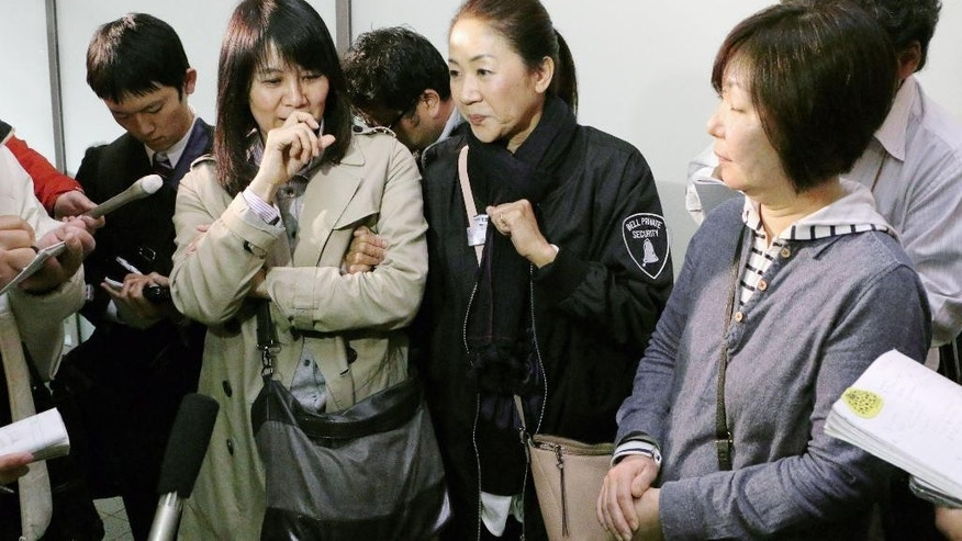 Passengers who escaped from an Asiana Airlines plane that skidded off a runway after landing at Hiroshima Airport speak to the media at the airport in Mihara, Hiroshima Prefecture, western Japan, Tuesday, April 14, 2015. The Hiroshima airport reported that the tail of the Airbus 320 plane from Seoul, South Korea, touched the runway while landing, causing some sparks, but there were no flames, the Mihara City fire department said. About 20 people among 74 passengers and eight crew members were injured slightly, officials said. (Shinpei Sakaguchi/Kyodo News via AP) JAPAN OUT, CREDIT MANDATORY