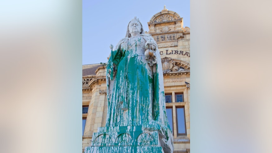 In this photo taken Friday, April, 10, 2015, a statue of Britain's Queen Victoria, outside the Port Elizabeth city library in South Africa, after being splashed with green paint. Excrement thrown at the statue of British colonialist Cecil John Rhodes began a wave of vandalizing protests in South Africa. Memorials to South Africa's colonial past were rejected as symbols of oppression by mainly young black protesters, as statues of British monarchs Queen Victoria and King George VI were splashed with paint, in the cities of Port Elizabeth and Durban respectively. (AP Photo/Michael Sheehan)
