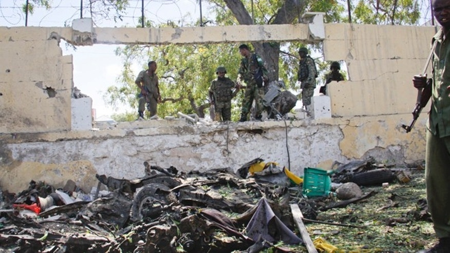 April 14, 2015: Soldiers stand near the wreckage of a car bomb that was detonated at the gates of a government office complex in the capital Mogadishu, Somalia.