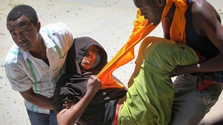 April 14, 2015: A person is assisted after being wounded when a car bomb detonated at the gates of a government office complex in the capital Mogadishu, Somalia.