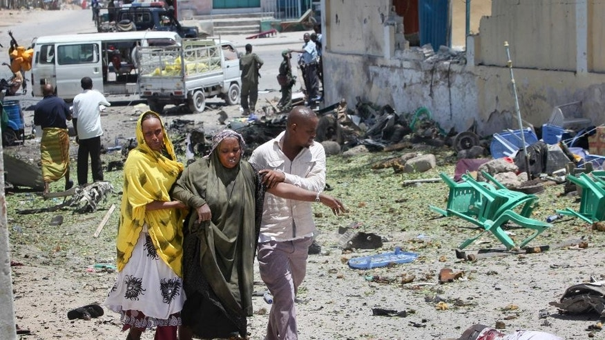 People assist a woman who was wounded when a car bomb detonated at the gates of a government office complex in the capital Mogadishu, Somalia Tuesday, April 14, 2015. A number of people were killed on Tuesday when attackers stormed the ministry of higher education after a suicide car bomber detonated his vehicle at the gate of the office complex, opening the way for gunmen to enter, according to a senior police officer. (AP Photo/Farah Abdi Warsameh)