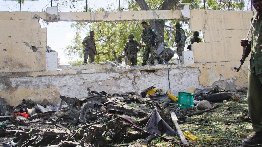 Soldiers stand near the wreckage of a car bomb that was detonated at the gates of a government office complex in the capital Mogadishu, Somalia Tuesday, April 14, 2015. A number of people were killed on Tuesday when attackers stormed the ministry of higher education after a suicide car bomber detonated his vehicle at the gate of the office complex, opening the way for gunmen to enter, according to a senior police officer. (AP Photo/Farah Abdi Warsameh)