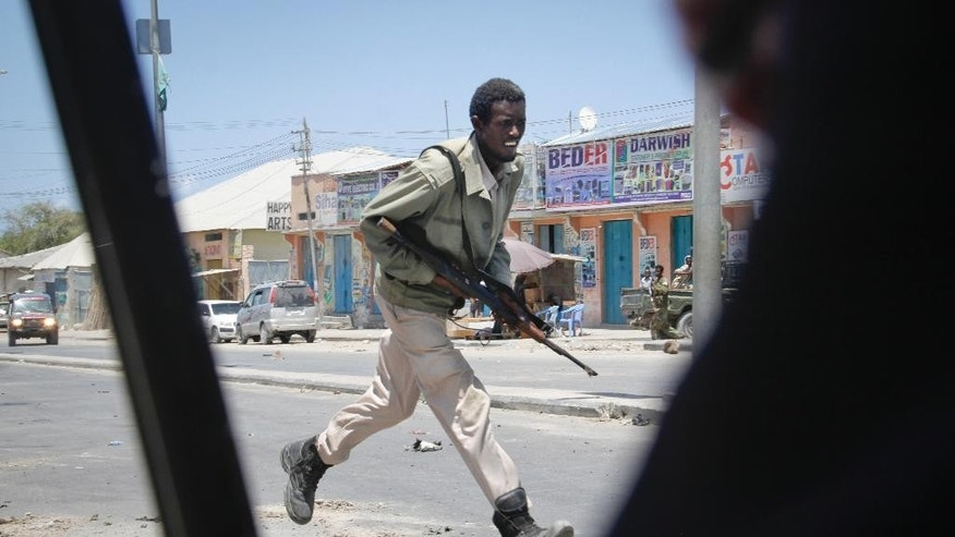 A Somali soldier runs during fighting following a car bomb that was detonated at the gates of a government office complex in the capital Mogadishu, Somalia Tuesday, April 14, 2015. A number of people were killed on Tuesday when attackers stormed the ministry of higher education after a suicide car bomber detonated his vehicle at the gate of the office complex, opening the way for gunmen to enter, according to a senior police officer. (AP Photo/Farah Abdi Warsameh)