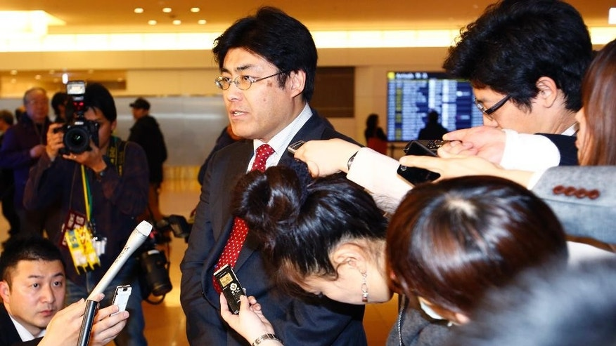 Japanese journalist Tatsuya Kato of Sankei Shimbun newspaper, answers a reporter's question upon his arrival at Haneda International Airport in Tokyo Tuesday, April 14, 2015. South Korea lifted an overseas travel ban on Kato, a former Seoul bureau chief of the conservative Japanese newspaper, charged with defaming the South Korean president, officials said earlier in the day. (AP Photo/Shizuo Kambayashi)