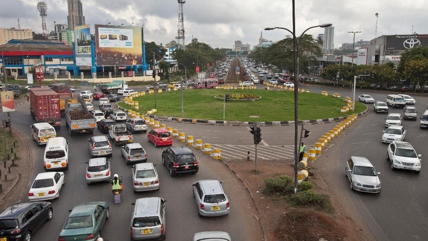 Drivers sit in queues of traffic at a traffic circle with its exits blocked off by barriers to prevent right turns, on a highway in downtown Nairobi, Kenya Tuesday, April 14, 2015. A plan launched this month to ease road congestion in Nairobi by replacing key traffic circles with intersections and stoplights has, at least initially, made things worse in some areas with television newscasts filled with cars at a standstill and fuming drivers, some of whom wondered what the gridlock says about leadership and planning in Kenya as a whole. (AP Photo/Sayyid Azim)
