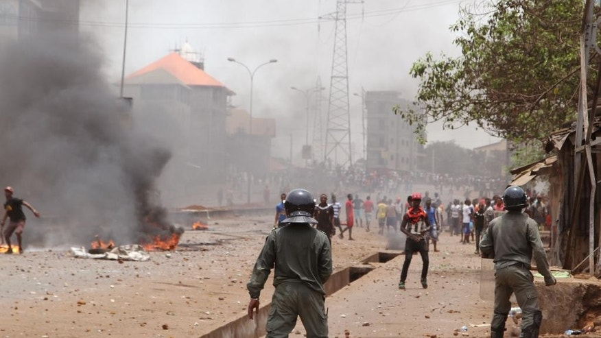 In this photo taken on Monday, April 13, 2015, Guinea security forces, foreground, face people rioting and burning rubbish and other goods  in the streets of Conakry, Guinea. Witnesses say violent clashes have erupted for a second day in Guinea's capital between security forces and opposition party protesters. The renewed violence Tuesday came a day after one young man died from a gunshot wound blamed on police. (AP Photo/ Youssouf Bah)