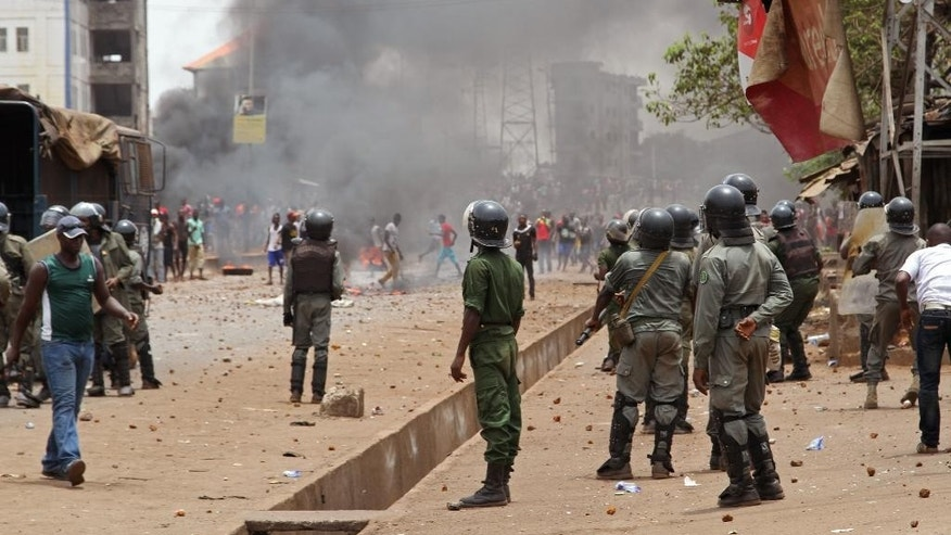 In this photo taken on Monday, April 13, 2015, Guinea security forces, center, face people rioting and burning rubbish and other goods  in the streets of Conakry, Guinea. Witnesses say violent clashes have erupted for a second day in Guinea's capital between security forces and opposition party protesters. The renewed violence Tuesday came a day after one young man died from a gunshot wound blamed on police. (AP Photo/ Youssouf Bah)