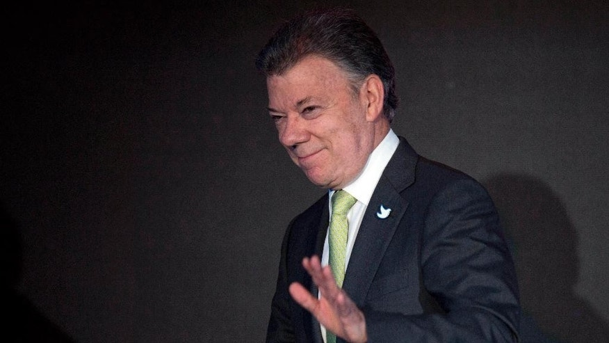 FILE - In this April 10, 2015, file photo, Colombia's President Juan Manuel Santos waves after delivering his speech during the CEO Summit of the Americas in Panama City. Colombia's president ordered,on Wednesday, April 15, 2015, the resumption of air raids on rebel camps after an attack by leftist guerrillas killed 11 soldiers and wounded 19, jeopardizing progress in two-year-old peace talks. (AP Photo/Moises Castillo, File)