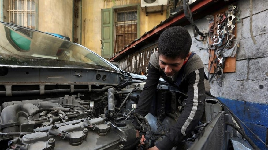 Syrian Mohammed Mousa, 13, who fled his home in Aleppo, Syria, works as a cars mechanic, in Beirut, Lebanon, Wednesday, April 15, 2015. An estimated 21 million children in the Middle East and North Africa are out of school or at risk of dropping out despite improved access to education in the region over the past decade, the United Nations said in a report released Wednesday. (AP Photo/Bilal Hussein)