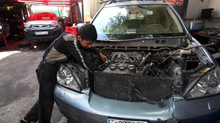 Syrian Mohammed Mousa, 13, who fled his home in Aleppo, Syria, works as a car mechanic in Beirut, Lebanon, Wednesday, April 15, 2015. An estimated 21 million children in the Middle East and North Africa are out of school or at risk of dropping out despite improved access to education in the region over the past decade, the United Nations said in a report released Wednesday. (AP Photo/Bilal Hussein)