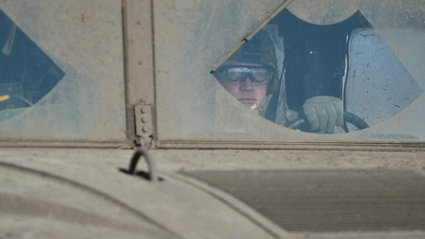 """An US soldier drives an armored vehicle at Smardan shooting range, near Galati, Romania, Wednesday, April 15, 2015.  Some 2,200 Romanian, U.S., British and Moldovan troops will take part in """"Wind Spring 15"""" military exercises at a shooting range and an airbase near the Black Sea close to the border with Moldova and Ukraine, Romanian Defense Minister Mircea Dusa confirmed Wednesday. (AP Photo/Octav Ganea, Mediafax) ROMANIA OUT"""