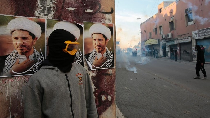 FILE - In this Jan. 20, 2015, file photo, a Bahraini anti-government protester watches clashes between protesters and police firing tear gas and shotguns, in Bilad al-Qadeem, Bahrain. Government reforms put in place by Bahraini authorities in the wake of widespread anti-government protests four years ago have failed to end serious violations of human rights in the strategically important Gulf nation, Amnesty International said in a report released Thursday, April 16, 2015. (AP Photo/Hasan Jamali, File)