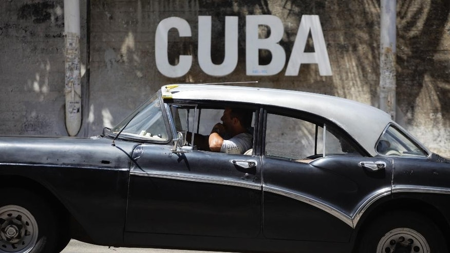 "A man drives his taxi past a Cultural Center with the word ""Cuba"" on it, in Havana, Cuba, Tuesday, April 14, 2015. President Barack Obama will remove Cuba from the list of state sponsors of terrorism, the White House announced Tuesday, a key step in his bid to normalize relations between the two countries. (AP Photo/Desmond Boylan)"