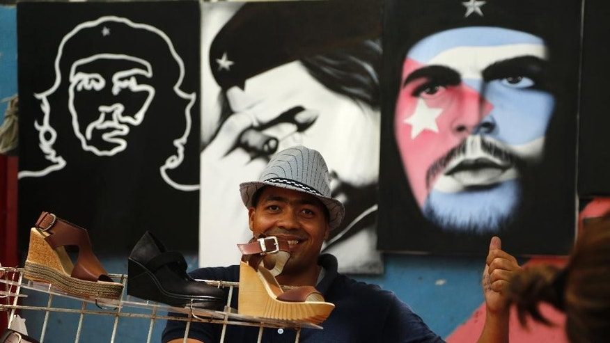 "A vendor gives a thumbs up to the camera as he sells shoes and paintings of Cuba's revolutionary hero Ernesto ""Che"" Guevara in Havana, Cuba, Tuesday, April 14, 2015. President Barack Obama will remove Cuba from the list of state sponsors of terrorism, the White House announced Tuesday, a key step in his bid to normalize relations between the two countries. (AP Photo/Desmond Boylan)"