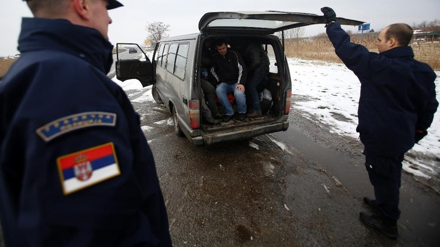 FILE - In this Tuesday, Feb. 10, 2015 file photo, Serbian border police officers detain Kosovo migrants near the northern Serbian town of Subotica, not far from the border between Serbia and Hungary. Human Rights Watch said in its report released Wednesday, April 15 that thousands of people fleeing Afghanistan, Syria and other violence-ravaged countries in Asia and Africa have been targets of assaults, threats, insults and extortion as they pass through Serbia on their way to the border with Hungary where they try to sneak into the European Union. (AP Photo/Darko Vojinovic, File)