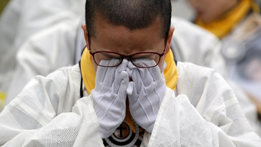 In this April 5, 2015, file photo, a relative of the victim of a South Korean ferry sinking cries during a rally demanding to salvage the ferry Sewol off the country's southwest coast before starting the compensation process and thoroughly investigating of truth in Seoul, South Korea. A year ago, as South Korea writhed in grief and fury after more than 300 people, most of them school kids, drowned in the ferry sinking, it seemed things would never be the same. Yet not much has really changed as the first anniversary of the Sewol disaster is marked Thursday, April 16, 2015.  (AP Photo/Lee Jin-man, File)