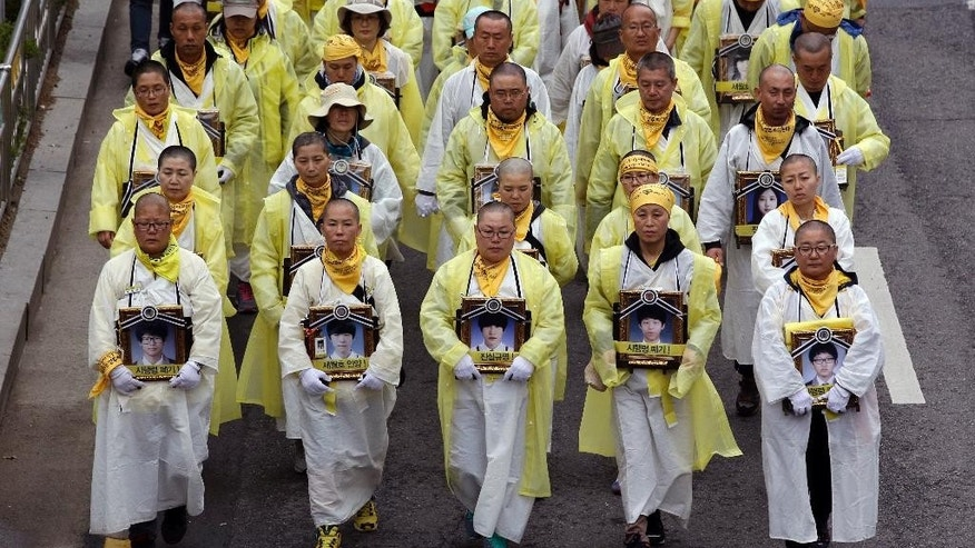 FILE - In this April 5, 2015 file photo, relatives carrying the portraits of the victims of a South Korean ferry sinking march during a rally demanding to salvage the ferry Sewol off the country's southwest coast before starting the compensation process and thoroughly investigating of truth in Seoul, South Korea. A year ago, as South Korea writhed in grief and fury after more than 300 people, most of them school kids, drowned in the ferry sinking, it seemed things would never be the same. Yet not much has really changed as the first anniversary of the Sewol disaster is marked Thursday, April 16, 2015.  (AP Photo/Lee Jin-man, File)