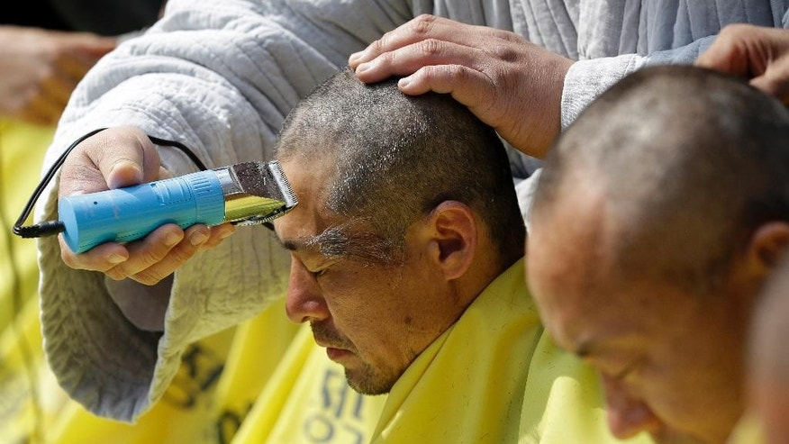 FILE - In this April 2, 2015, file photo, relatives of victims of the South Korean ferry sinking have their heads shaved during a rally against the government's plans in Seoul, South Korea. The government blamed the country's deadliest maritime disaster in decades on overloaded, poorly secured cargo and a botched rescue. But South Korea is divided over who's responsible, and a planned investigation by a special committee has stalled amid wrangling over money and personnel. The Sewol ferry sank on April 16, 2014, killing 304 people including 250 Danwon High School students on a school trip. (AP Photo/Lee Jin-man, File)